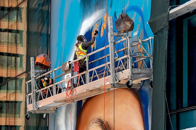 Matt Adnate at work on his multicultural mural which features the faces of a Noongar man, an Indian woman and a Mediterranean woman.