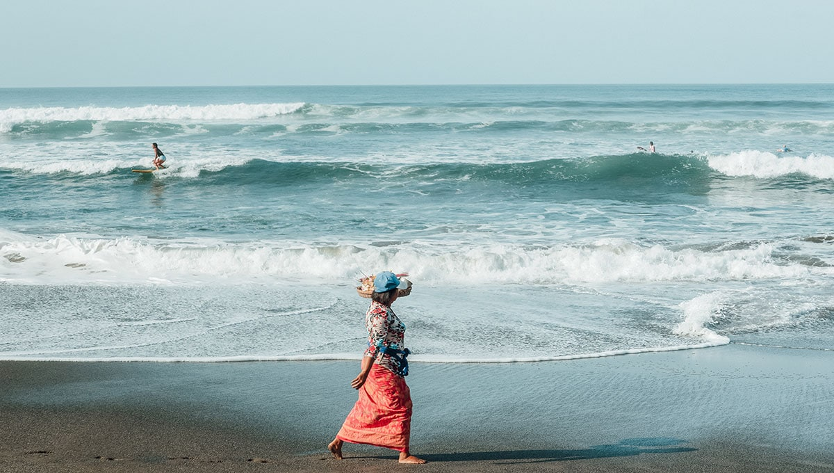 A local woman makes her morning offerings along Batu Balong beach, as surfers carve up the famous Canggu waves.